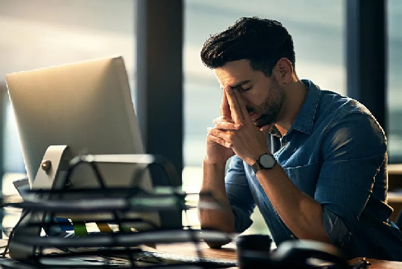 Man at computer looking worried.